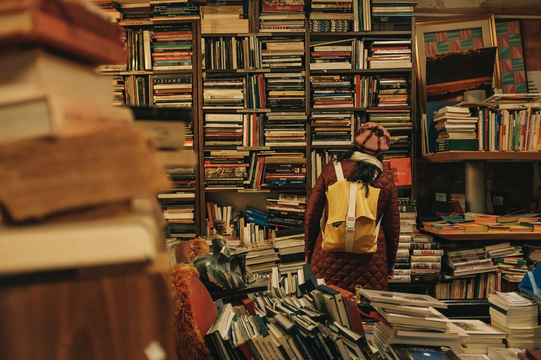 Person in front of many many haphazardly stacked books on shelves. By Darwin Vegher on Unsplash. @darwiiiin
